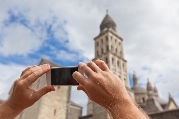 フランスでペリグーの写真を撮っている間スマートフォンを持っている観光手