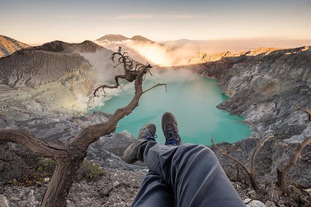 Ноги туриста свисают на кратере кавах иджен с изумрудным озером на восходе солнца. восточная ява, индонезия