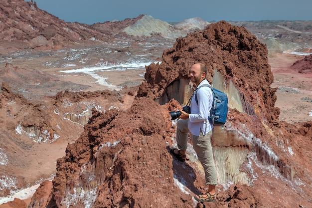 여행자는 짠 산에서 가파른 트랙을 하이킹하며 배낭과 카메라로 아름다운 풍경을 감상하는 한 배낭.