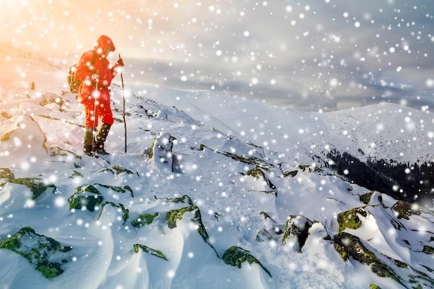 밝은 빨간색 옷을 입은 관광 등산객은 폭풍우 치는 흐린 하늘 복사 공간 배경에 눈으로 덮인 위험한 바위 산 경사면을 걷고 지팡이를 짚고 내려갑니다.