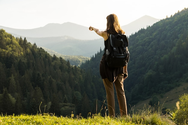 Tourist hiker young woman points at stunning view of sunset in mountains