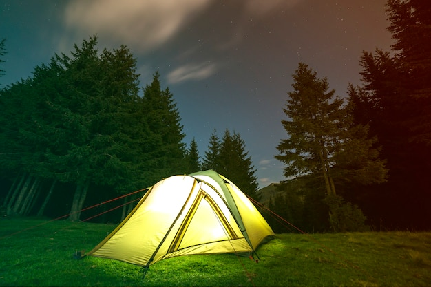 Tourist hikers tent brightly lit from inside on green grassy forest clearing