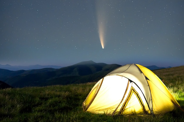 Tourist hikers tent in mountains at night with stars and neowise comet with light tail in dark night