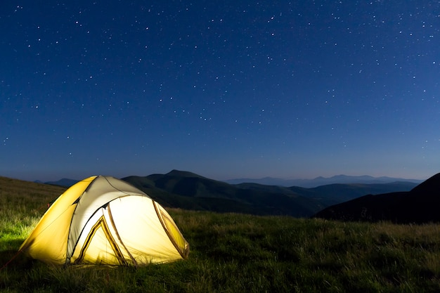 Tourist hikers tent in mountains at night with stars in the sky
