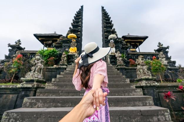 Турист держит мужчину за руку и ведет его к храму бесаких на бали, индонезия