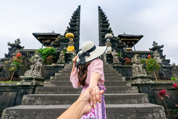 Tourist holding man's hand and leading him to besakih temple in bali, indonesia