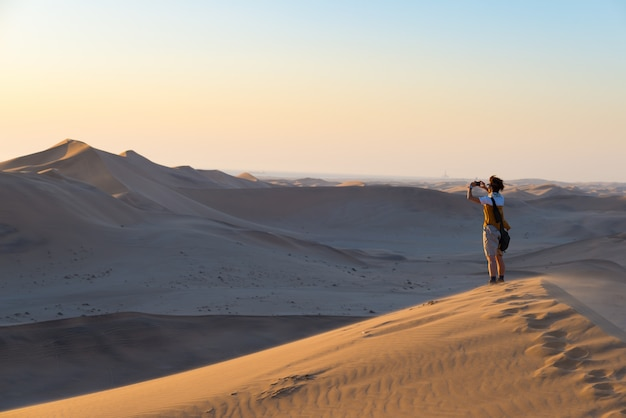 Tourist holding smart phone and taking photo at scenic sand dunes illuminated