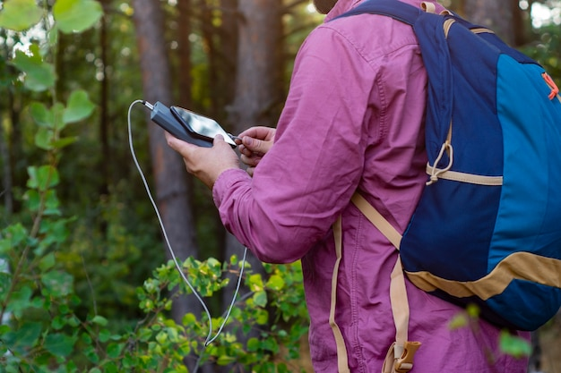관광객은 손에 휴대용 충전기가 든 스마트폰을 들고 있습니다. power bank를 가진 남자는 자연과 숲을 배경으로 전화를 충전합니다.
