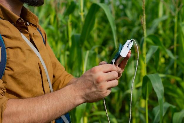 관광객은 손에 휴대용 충전기가 든 스마트폰을 들고 있습니다. 전원 은행을 가진 남자는 옥수수 밭을 배경으로 전화를 청구합니다.