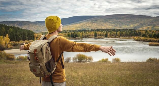 노란 모자를 쓰고 배낭을 메고 스웨터를 입은 관광객이 강, 가을 황금빛 숲, 언덕 앞 양옆으로 팔을 뻗고 서 있습니다. 자유, 여행, 하이킹의 개념