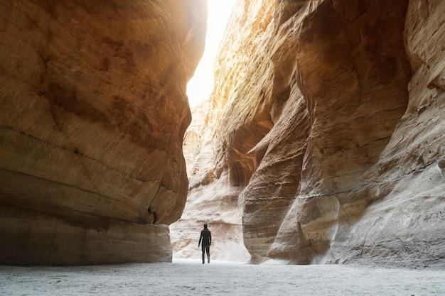 Турист в узком проходе скал каньона петры в иордании. объект всемирного наследия юнеско. путь через ущелье сик в каменный город петра. одинокий человек, идущий среди скал. солнечный свет пробивает скалы.