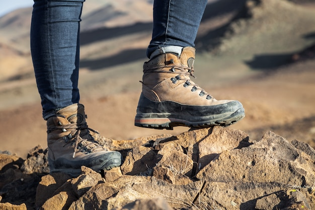 Турист в походных ботинках гуляя на гору на заходе солнца