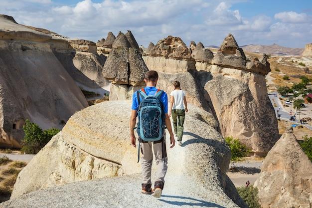 Турист в необычной скальной формации в каппадокии, турция
