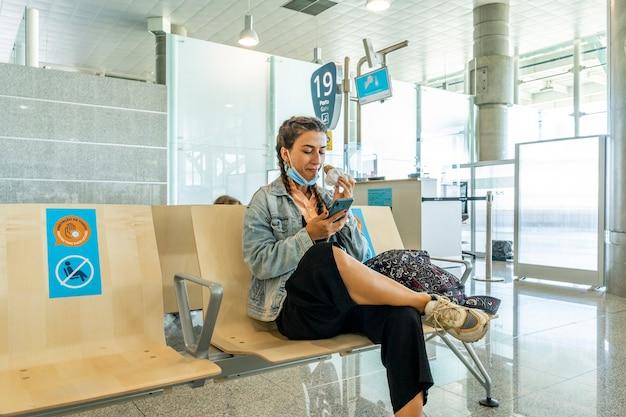 空港内の観光客、出発エリア、座ってサンドイッチを食べる