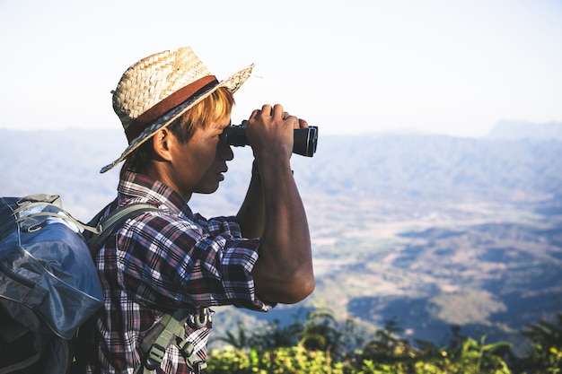 Tourist is watching through binoculars on sunny cloudy sky from mountain top.