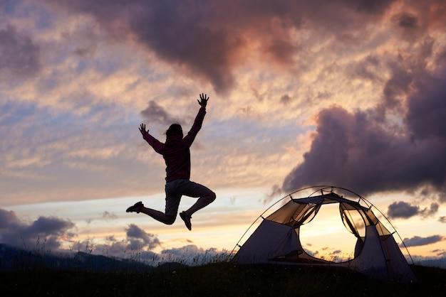 Турист прыгает высоко, обожая красивые пейзажи на холме горы