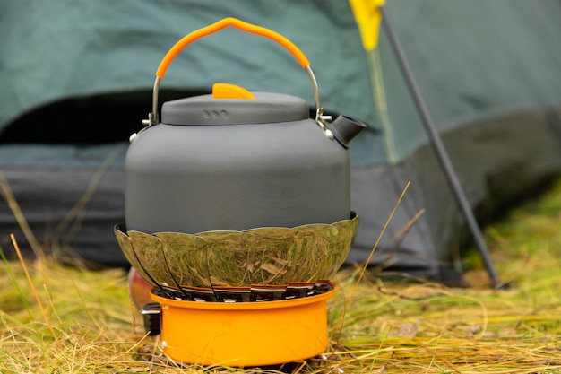 Tourist kettle on a gas burner. cooking in field conditions. using a tourist gas burner