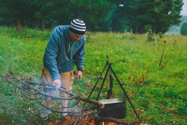 Турист разжигает огонь.
