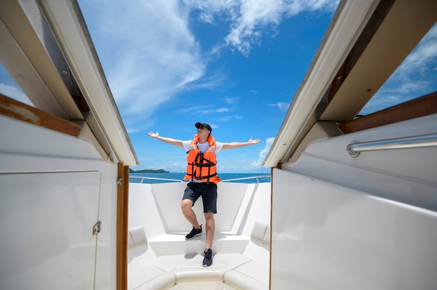A tourist in life jacket enjoying and relaxing on speedboat with a beautiful view of ocean and mountain