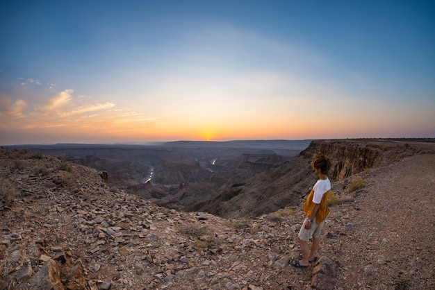 Tourist looking at the fish river canyon, scenic travel destination in southern namibia. ultra wide angle view from above, colorful scenic sunset.