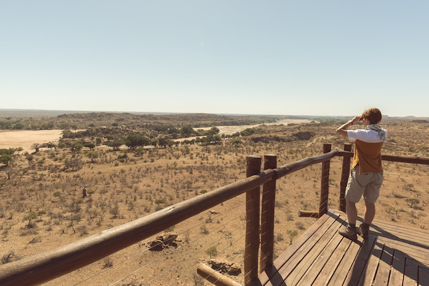 Tourist looking at panorama with binocular from viewpoint over the mapungubwe national park, south africa.