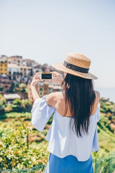 Tourist looking at scenic view of vernazza, cinque terre, liguria, italy