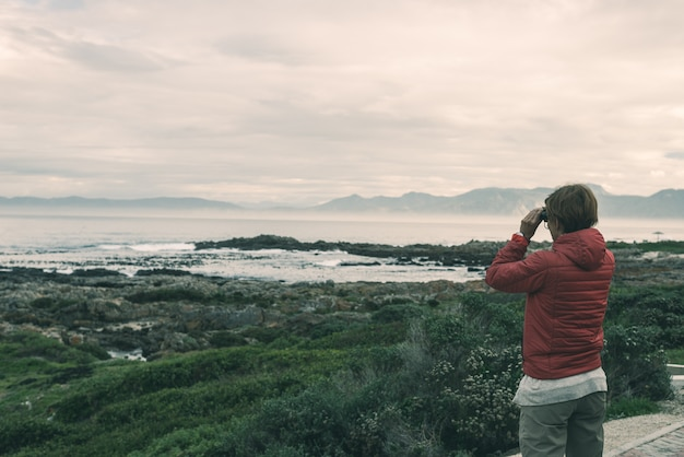 Tourist looking with binocular on the rocky coast line at de kelders, south africa, famous for whale watching.