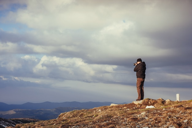 Tourist looks at the landscape. photographer on top of mountain