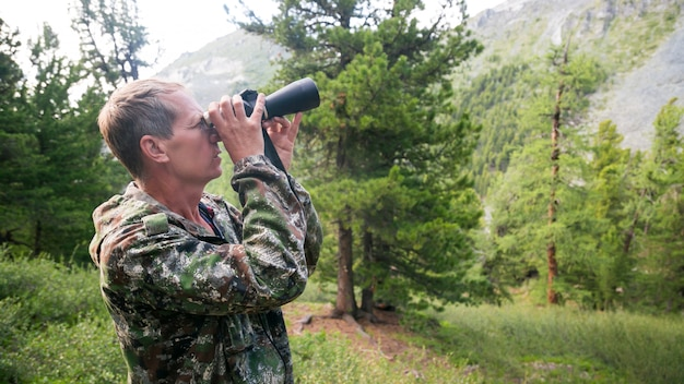 The tourist looks through the binoculars to the mountains.