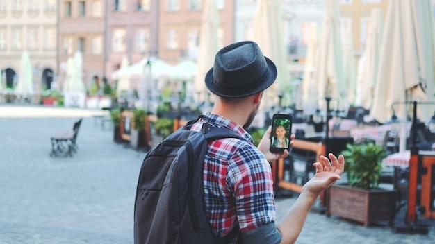 Турист делает видеозвонок на смартфон с туристкой из другого места