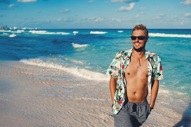 Туристический мужчина в гавайской рубашке на фоне моря или океана