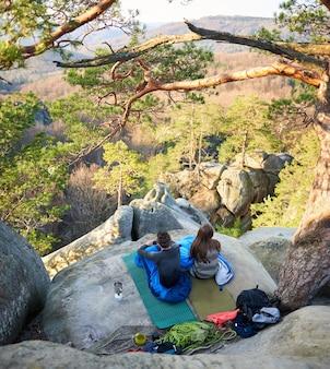 Туристический мужчина и женщина в спальных мешках на больших скалах