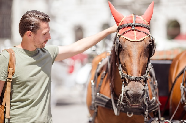 Tourist man enjoying a stroll through vienna and looking at the two horses in the carriage