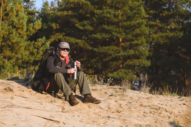 Туристический человек отдыхает с термосом в лесу