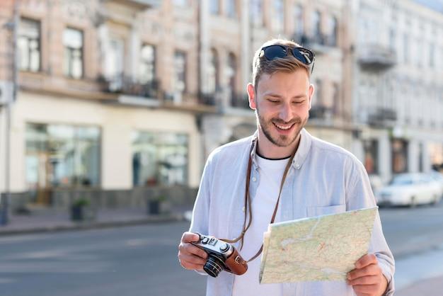 カメラと地図を保持している観光客の男