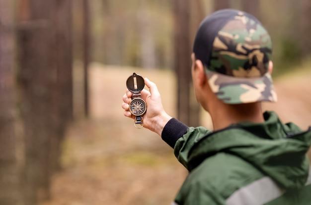 관광 남자는 숲에서 나침반을 사용하여 올바른 방향으로 검색하고 있습니다.