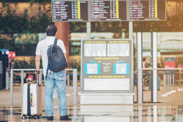 Tourist man looking at flight information board in airport