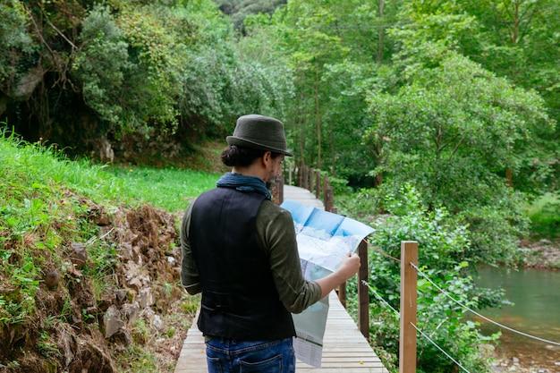 休暇のランドマークの地図を見る観光客の男