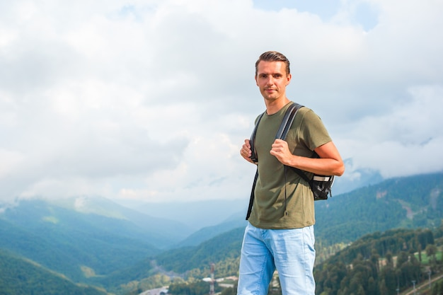 Tourist man in mountains in the scene of fog