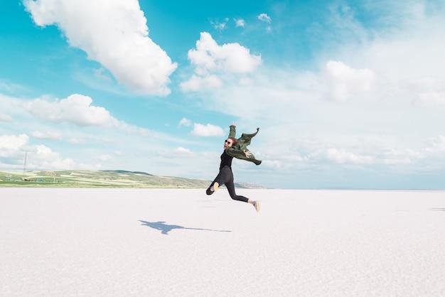 Tourist man posing and jumping on the famous tourist destination salt lake