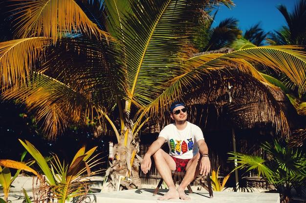 Туристический человек сидит на стуле и смотрит в сторону на фоне пальм