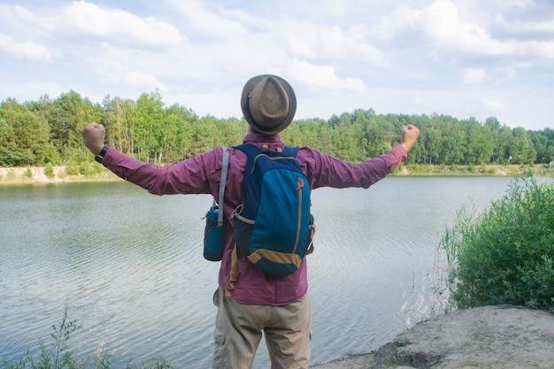 관광 남자는 여행을 위한 배낭을 메고 호수 기슭에 서 있습니다.