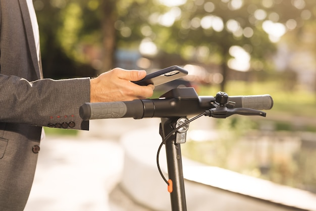 Мужчина-турист берет электросамокат на парковке, экологически чистый транспорт, красивый мужчина в ...