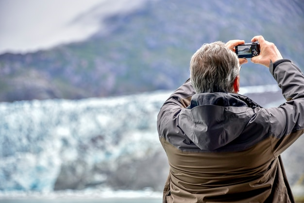 A tourist man taking picture of a glacier with his camera for travel background