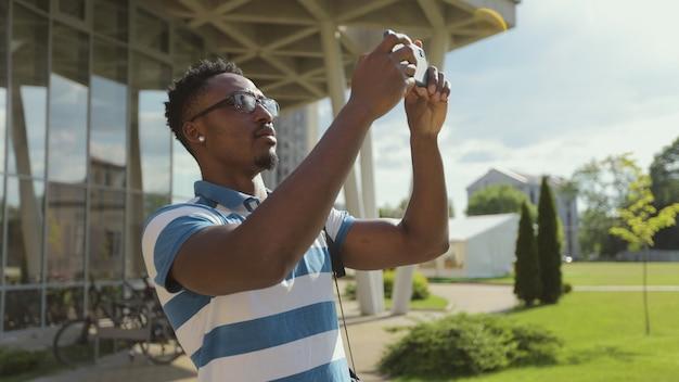 Туристический человек фотографирует с камерой телефона за пределами молодого афроамериканца, фотографирующего по телефону на улице