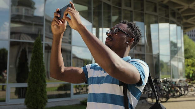 Tourist man taking picture with camera phone outside young african american man taking photo on phone on street