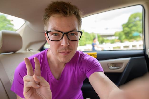 Tourist man taking selfie in back seat of taxi in bangkok thailand