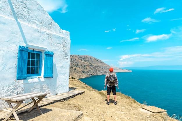 집 근처 바다와 산의 아름다운 전망을 즐기는 배낭 여행자
