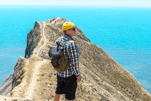 바다의 아름다움을 즐기는 곶 꼭대기에 배낭을 메고 있는 관광 남자. 여름 여행 개념