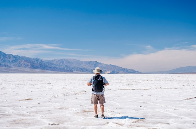 A tourist man with a hat to curb from the sun and a traveler's backpack enjoys a sunny day in the death valley desert